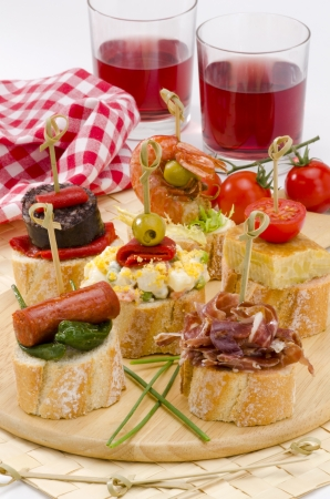 spanish tapas: Spanish cuisine  Montaditos  Sliced bread topped with a variety of appetizers  Spanish Tapas Two glasses of red wine in the background  Stock Photo