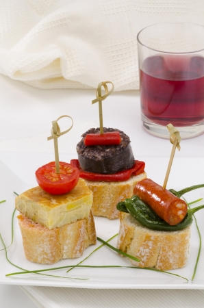 spanish culture: Spanish cuisine. Montaditos. Sliced bread topped with a variety of appetizers. Spanish Tapas. A glass of red wine in the background. Stock Photo