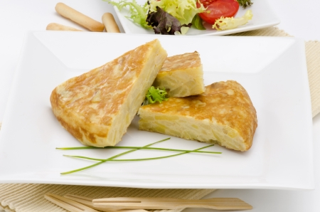 de focus: Spanish Cuisine  Spanish Omelette served in slices  Tortilla de patatas  White background  Focus on foreground