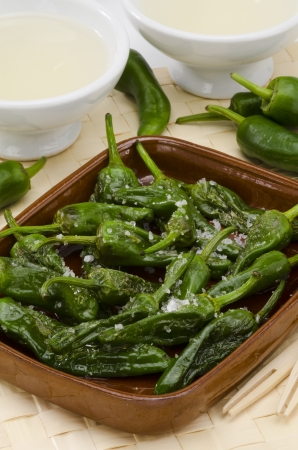 Fried green peppers in salt. Pimientos del Padron. White background. Spanish Cuisine. Ribeiro wine in foreground. photo