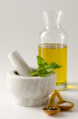 oilcan: Herbs and spices composition including olive oil, pepper, salt and mint. White background.
