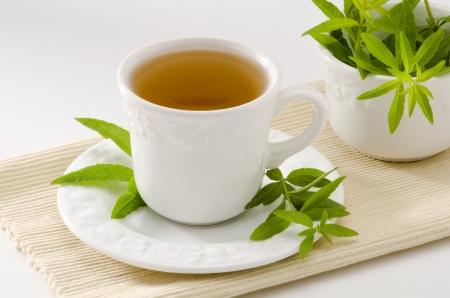 Verbena tisana in una tazza. Aloysia citriodora. Naturopatia. Sfondo bianco. Concentrarsi sul primo piano.