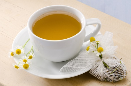 matricaria: Chamomile Herbal Tea in a white cup. Naturopathy. Focus on Foreground. Matricaria chamomilla.