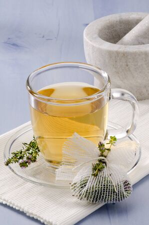 naturopathy: Thyme Herbal Tea in a glass cup. Thymus vulgaris. Naturopathy. Focus on foreground.