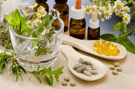 Alternatieve Geneeskunde. Rozemarijn, munt, kamille, tijm in een glazen mortier. Essentiële oliën en kruiden-supplementen. Stockfoto