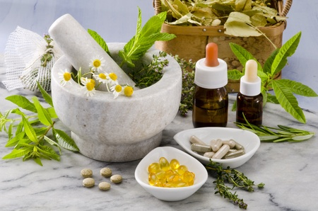 naturopathy: Alternative Medicine. Rosemary, mint, chamomile, thyme in a marble mortar. Essential oils and herbal supplements.