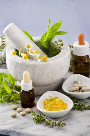 Alternative Medicine. Rosemary, mint, chamomile, thyme in a marble mortar. Essential oils and herbal supplements. photo