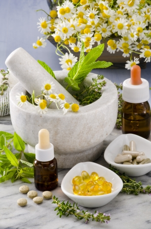 Alternative Medicine. Rosemary, mint, chamomille, thyme in a marble mortar. Essential oils and herbal supplements.