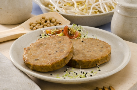 Vegetarian soy burger on a ceramic plate. Focus on foreground. Stock Photo