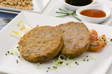 Vegetarian tofu burger on a ceramic plate. Soy products. Focus on foreground. Stock Photo