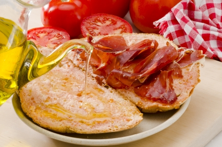 Spanish cuisine. Olive oil pouring over sliced  tomato bread. Selective Focus. Pa amb tomaquet i pernil.