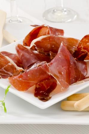 Spanish cuisine. Tapas. Sliced Serrano Ham in a white plate. Selective Focus. Jamon Serrano. photo