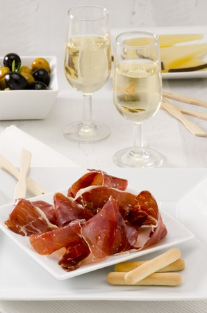 sherry: Spanish cuisine. Tapas. Sliced Serrano Ham in a white plate.Two glasses of Sherry Wine in the background. Selective Focus. Jamon Serrano. Stock Photo