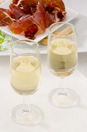 Spanish cuisine. Tapas. Two glasses of Sherry Wine. Sliced Serrano Ham in the background. Selective Focus. Vino de Jerez. photo