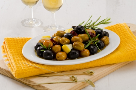 Spanish cuisine. Tapas. Marinated Olives in a white plate.Two glasses of Sherry Wine in the background. Selective Focus. photo