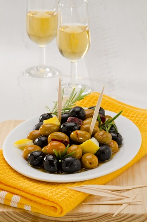Spanish cuisine. Tapas. Marinated Olives in a white plate.Two glasses of Sherry Wine in background. Selective Focus. photo