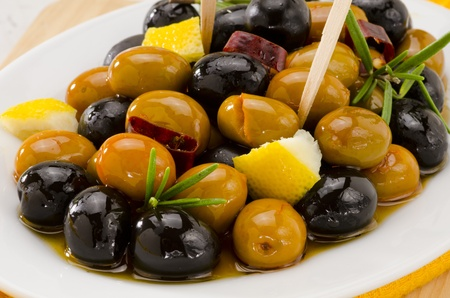 Spanish cuisine. Tapas. Marinated Olives in a white plate.Selective Focus. Stock Photo