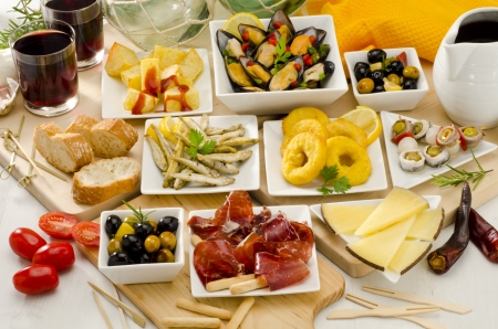 Spanish cuisine. Assortment of  Tapas including Serrano Ham, Manchego Cheese, Marinated Olives, Pikles, Potatoes in Hot Sauce, and others, served with red wine. Stock Photo