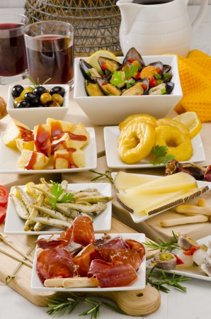 Spanish cuisine. Assortment of  Tapas including Serrano Ham, Manchego Cheese, Marinated Olives, Pikles, Potatoes in Hot Sauce, and others, served with red wine. photo