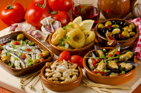 Spanish cuisine. Assortment of  Tapas including Serrano Ham,  Marinated Olives, Mussels in Sauce and others, served with red wine. Stock Photo