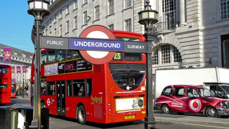 London, United Kingdom - July 19, 2013: Underground Sign at Regent Street and a double deck bus on the background; both are symbols of London.