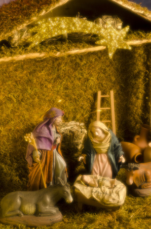 Christmas Crib. Figures of Baby Jesus, Virgin Mary and St. Joseph. Taken with a warm  and soft focus filter. Stock Photo