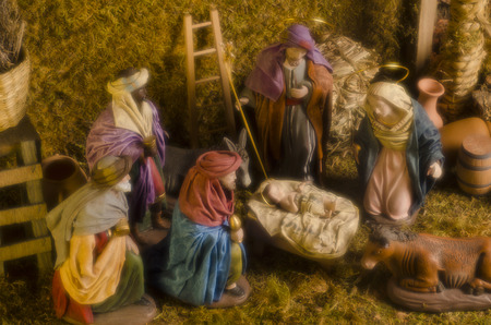 Christmas Crib. Adoration of The Three Wise Men. Baby Jesus in foreground. Taken with a soft focus and warm filter. photo