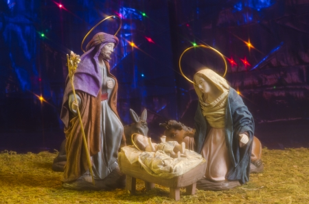 Christmas Crib. Figures of Baby Jesus, Virgin Mary and St. Joseph. Blue starry background. photo