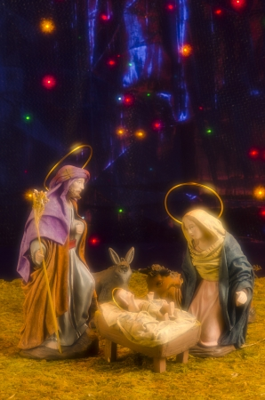 Christmas Crib. Figures of Baby Jesus, Virgin Mary and St. Joseph. Blue starry background. Soft Focus.