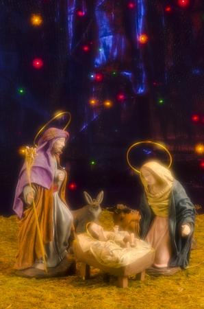bebe cuna: Pesebre de Navidad. Las figuras del Ni�o Jes�s, la Virgen Mar�a y San Jos�. Azul estrellado de fondo. Enfoque suave.