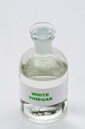 White vinegar in a glass bottle. White background.