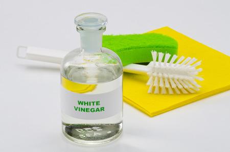 ガラス瓶の白酢。白い背景。有機洗剤。