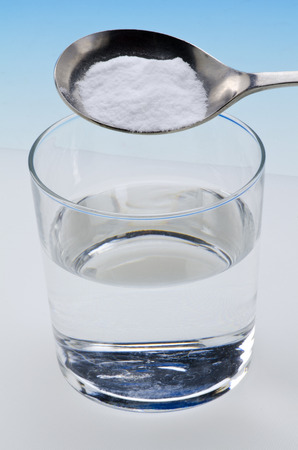 sodium bicarbonate: Sodium bicarbonate pouring in a glass of water.