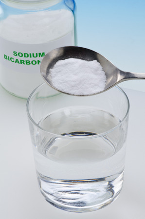 sodium bicarbonate: Sodium bicarbonate pouring in a glass of water. Stock Photo