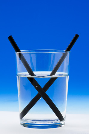 A straw in a glass of water shows light refraction. Blue background. Stock Photo