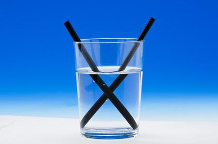 물 한 잔에 빨대는 빛의 굴절을 보여줍니다. 파란색 배경입니다.