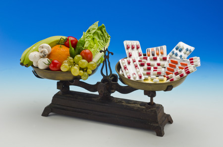 Healty food. Fresh fruits and vegetables versus medical pills on a scale. Blue background.