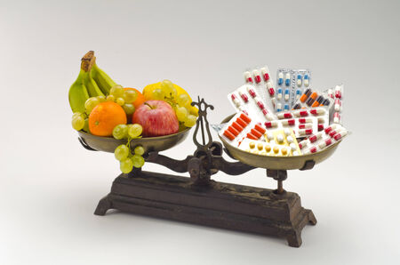 Healty food. Fresh fruits and vegetables versus medical pills on a scale. White background. Stock Photo