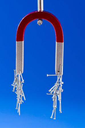 magnetismo: Magnete a ferro di cavallo con un mazzo di chiodi. Sfondo blu.