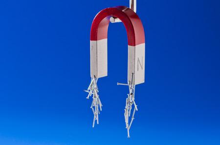 herradura: Im�n de herradura que sostiene un manojo de clavos. Fondo azul.