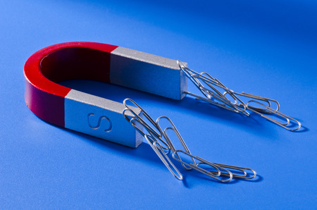 Horseshoe magnet holding a bunch of paperclips. Blue background. Imagens