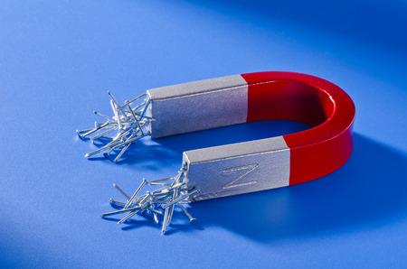 馬蹄形磁石釘の束を持っています。青色の背景色。 写真素材 - 36239596