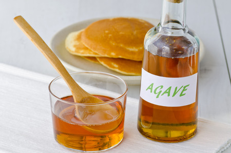Agave syrup and pancakes. Alternative sweetener to sugar. Selective focus. White background. Taken in daylight.