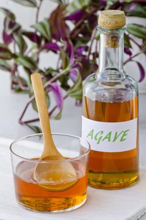 agave: Jarabe de agave en un vaso. Edulcorante alternativo al azúcar. Enfoque selectivo. Fondo blanco. Tomado en la luz del día. Foto de archivo