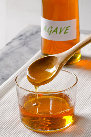 Agave Syrup pouring on a glass. Alternative sweetener to sugar. Selective focus.