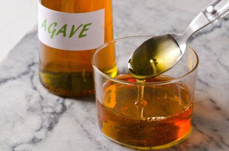 agave: Jarabe de Agave verter en un vaso. Edulcorante alternativo al azúcar. Enfoque selectivo.