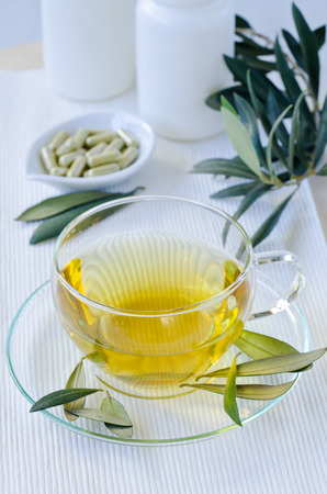 Olive leaf infusion and olive leaf extract capsules. Alternative medicine.  Selective focus. Taken in daylight. Stock Photo