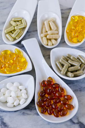 Variety of dietary supplements, including capsules of Garlic, Evening Primrose Oil; Artichoke Leaf;  Olive Leaf; Magnesium and Omega 3 Fish Oil. Selective focus. Taken in daylight. Stock fotó