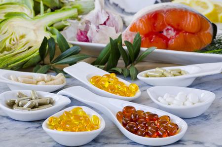 Varietà di integratori alimentari, tra cui capsule di aglio, olio di enotera; Carciofo Foglia; Olive Leaf; Magnesio e Omega 3 olio di pesce. Messa a fuoco selettiva. Preso alla luce del giorno.