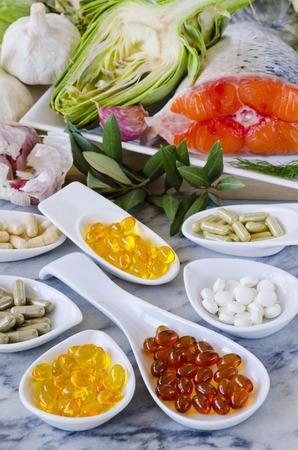 Verscheidenheid van voedingssupplementen, waaronder capsules van knoflook, teunisbloemolie; Artisjok Leaf; Olive Leaf; Magnesium en omega-3 visolie. Selectieve aandacht. Genomen bij daglicht. Stockfoto